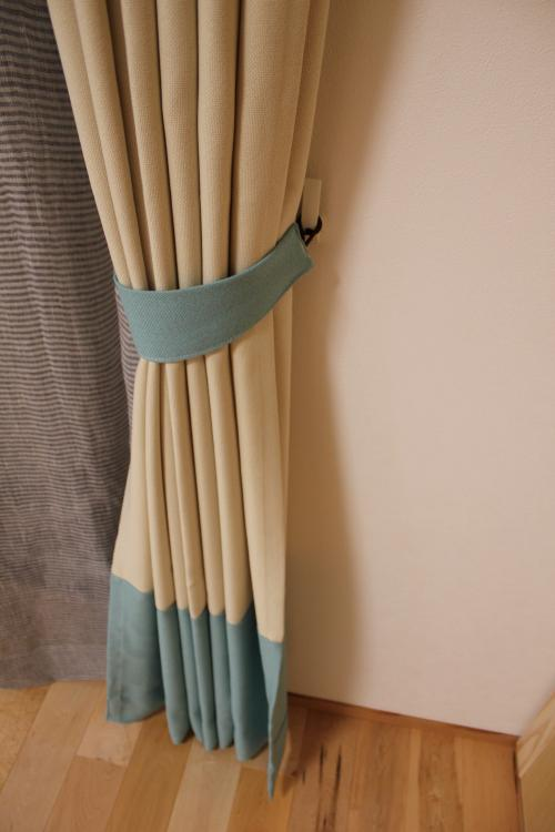 タッセルと裾の色がモスグリーンのベージュ地のカーテン