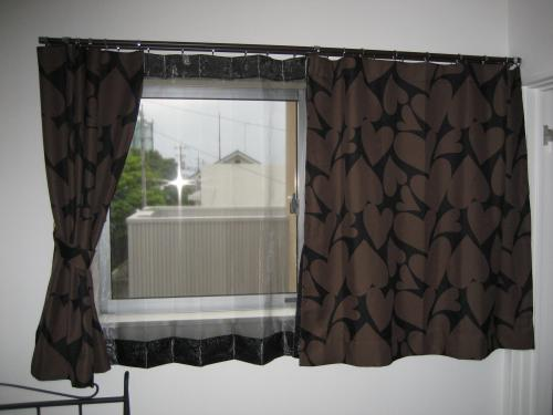 焦茶色に薄い茶色のハート柄のカーテンが掛かった窓。半分だけカーテンが開いている様子。