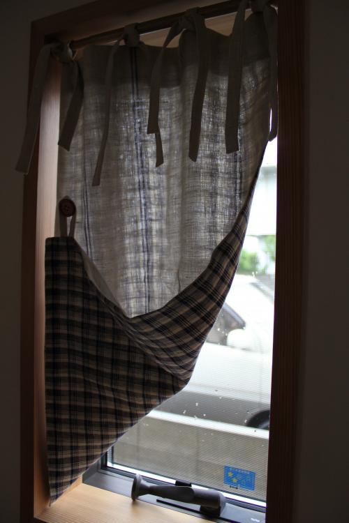 小窓に掛けられ、片方の裾をめくったチェック柄のカーテン