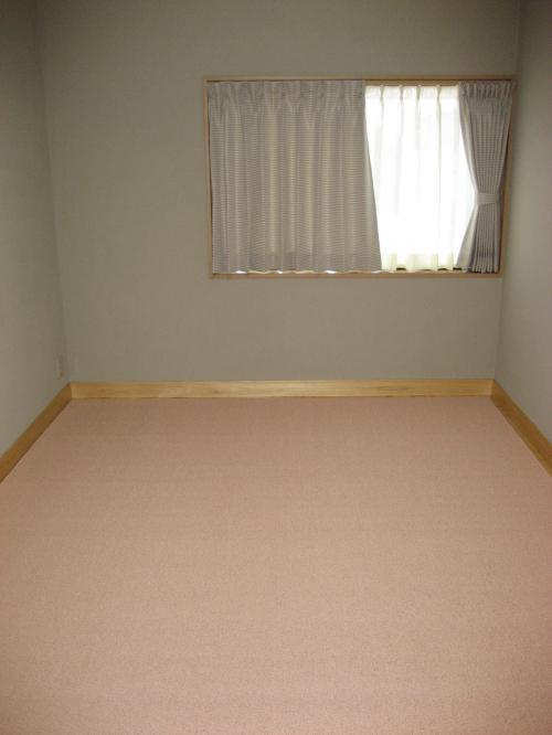淡いピンク系の色調のカーペットが床一面に敷かれている洋室の写真。部屋には窓と、窓枠にと同じサイズのカーテンのみ。
