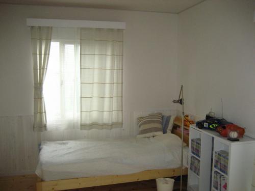 ベッドの向こうに薄黄緑色のカーテンが掛かった窓がある部屋