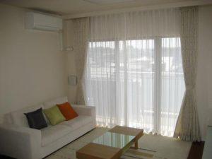 マンション室内写真、白を基調とした壁紙とソファーとラグ、天井から床までのロングレースカーテンが取り付けられている