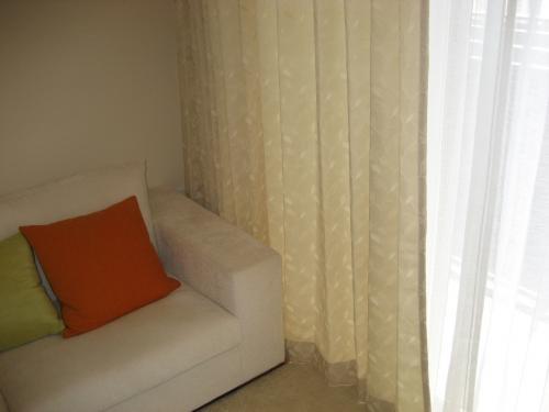 マンションの室内写真二枚目、レースカーテンの手前に同じ長さのクリーム色の遮光カーテンが取り付けられている