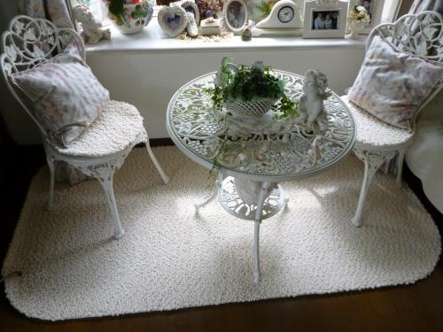 洋室の写真、白いラグに合わせた上品なデザインの白い丸テーブルとイス2脚