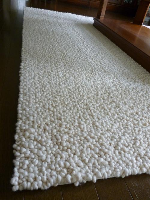 ランダムループで編まれた白いウールフェルトのラグの写真