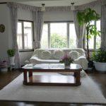 洋室の写真、中央に白いラグを敷き、テーブルと白いソファー