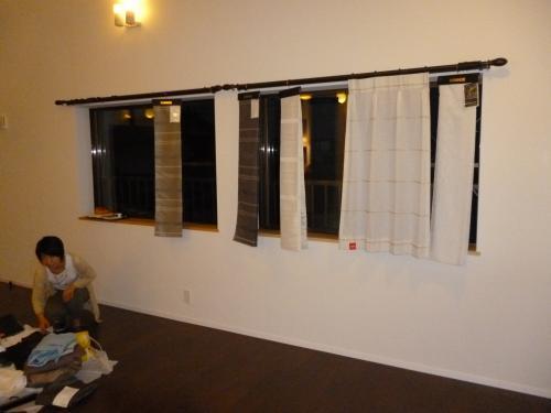 店内にて、数種類の中からお気に入りのカーテンを選別している写真、実際にレールに取り付けて選んでいる