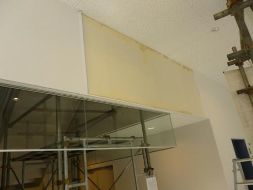 室内の工事風景写真二枚目、天井側を撮影、壁紙が一部剥がれている