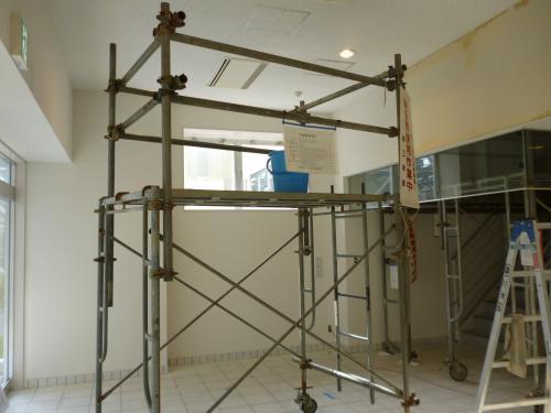室内の工事風景写真三枚目、写真中央に天井まで届く鉄骨の足場