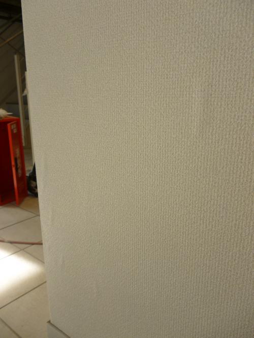 室内の工事風景写真四枚目、壁にクロスを貼っているが、小さく数か所湿って膨れている