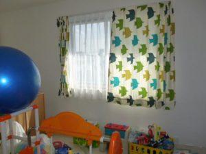 ベージュ地に青、緑、黄の鳥モチーフ柄のカーテンが掛かった窓