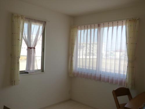 白いレースのカーテンが掛かった大小2つの窓