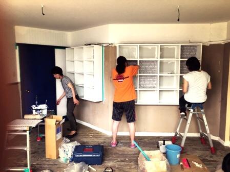 DIYの作業写真、壁に取り付けられた棚の壁紙を貼り換えている