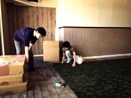 DIYの作業風景写真、床にタイルカーペットを二人で貼っている