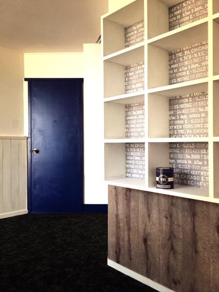 DIYの完成写真、塗り替えられたドアと壁紙を張り替えた棚、床にはシックなタイルカーペットが敷かれている