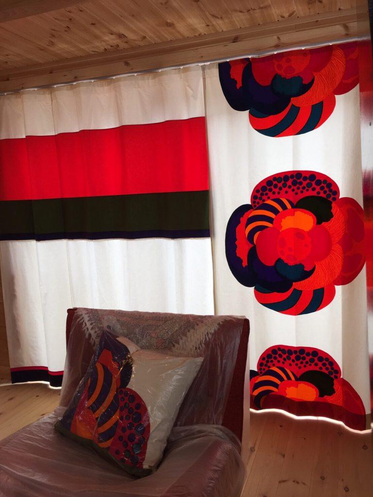 右側に大きな赤い花がデザインされ、左側は白赤黒色のカーテン