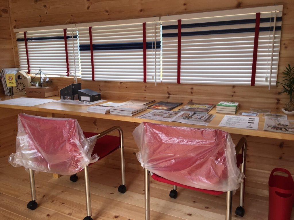 白色を基調とし、赤や青色も使われているブラインドがあるカフェコーナー