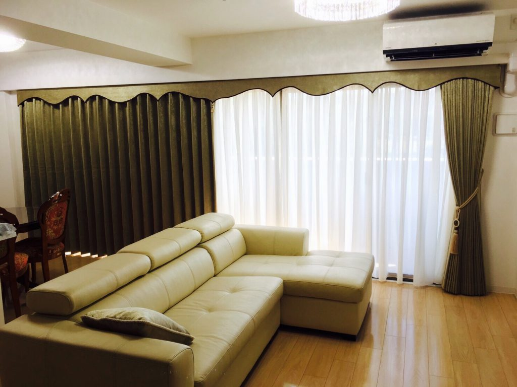 大きな窓にかかるカーテン。手前にソファーが置かれている