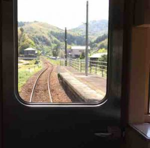 電車の窓から見える線路と山の景色。