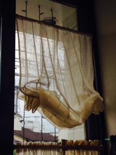 裾をたくし上げたレースのカーテンの窓