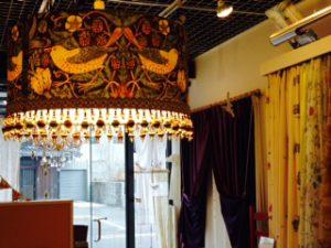 「いちご泥棒」の生地とSan-ai店内キラキラトリムの照明の写真