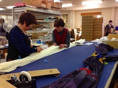 工場内で働く人がヒダにあわせてカーテンをたたむ様子