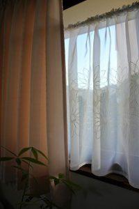 花の刺繍のカフェカーテンが掛かった窓の写真