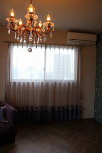 手前にシャンデリア、奥にレースのカーテンが掛かった窓が写る室内の写真