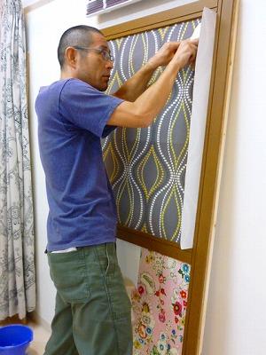 余分な壁紙をカッターで切り落としている作業風景写真