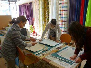 まちゼミでのインテリア講習会の写真、参加者の方々がカッターで壁紙を切る作業をしている