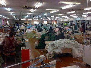 ミシンでカーテンを縫う人、大量のカーテンが写った縫製工場内の写真