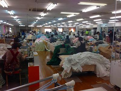 ミシンでカーテンを縫う人、大量のカーテンが写った縫製工場内の写真。