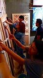 貼り方教室の風景写真、受講者が指導を受けながら木枠に布を貼っている
